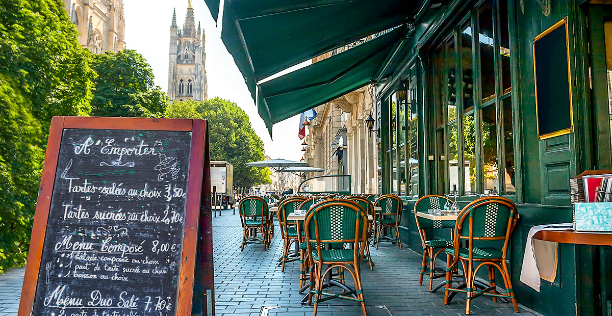 Street view of a Cafe terrace with tables and chairs in Bordeaux